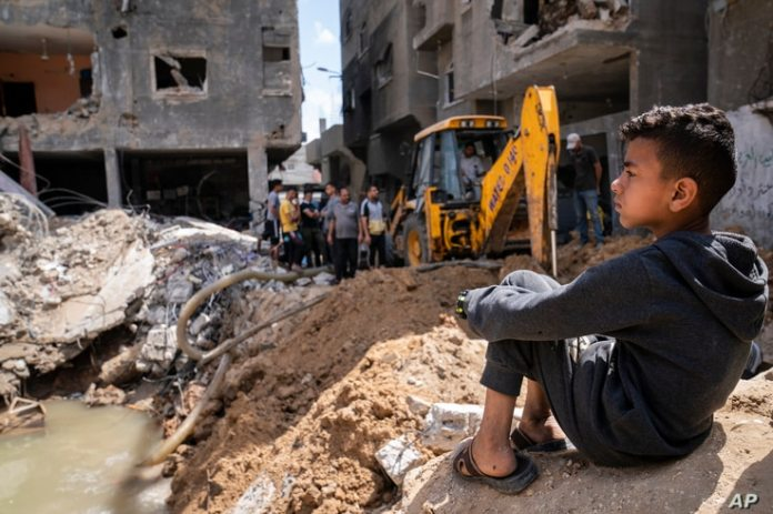 Children gather next to the crater where Ramez al-Masri's house was destroyed by an air strike before a ceasefire following an 11-day war between the Hamas rulers of Gaza and Israel, May 23, 2021, in Beit Hanoun, the northern Gaza Strip.