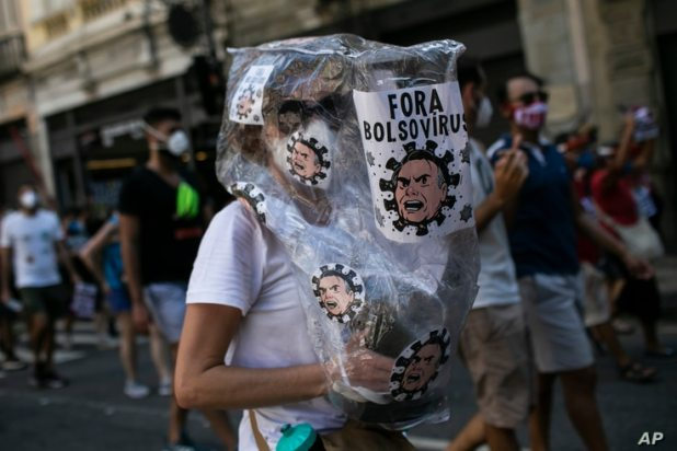 A woman wearing a plastic bag decorated with images depicting President Jair Bolsonaro as a virus, takes part in a protest against the government's response in combating COVID-19, May 29, 2021.