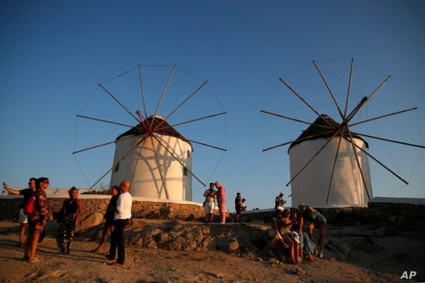 People gather as the sun sets at the Windmills on the Aegean Sea island of Mykonos, Greece, Sunday, Aug. 16, 2020. Greek…