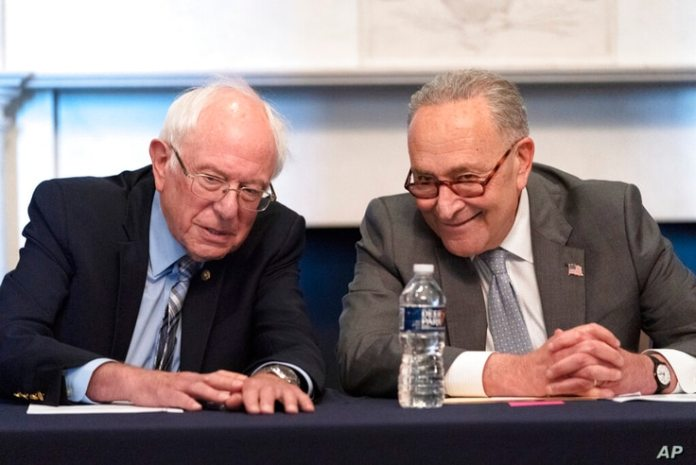 NY Senate Majority Leader Chuck Schumer sits right next to Sen during a meeting with the Senate.  Barney Sanders, I-VT.