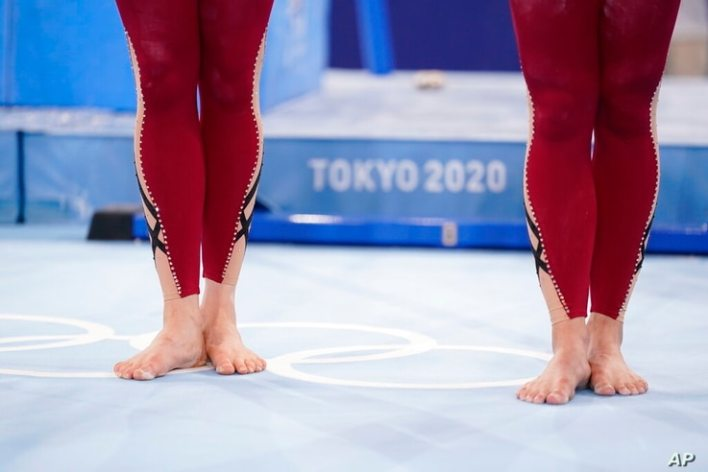 German gymnasts stand with their unitard costumes and wait to perform during the women's artistic gymnastic qualifications at…
