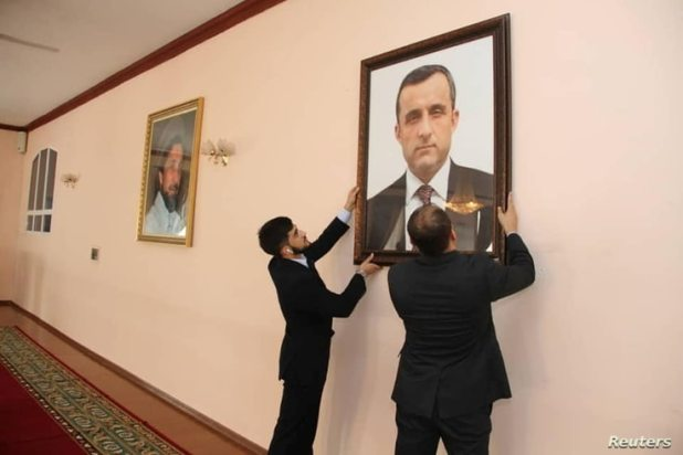 Afghan embassy staff hang a portrait of Afghan First Vice President Amrullah Saleh, who declared himself the