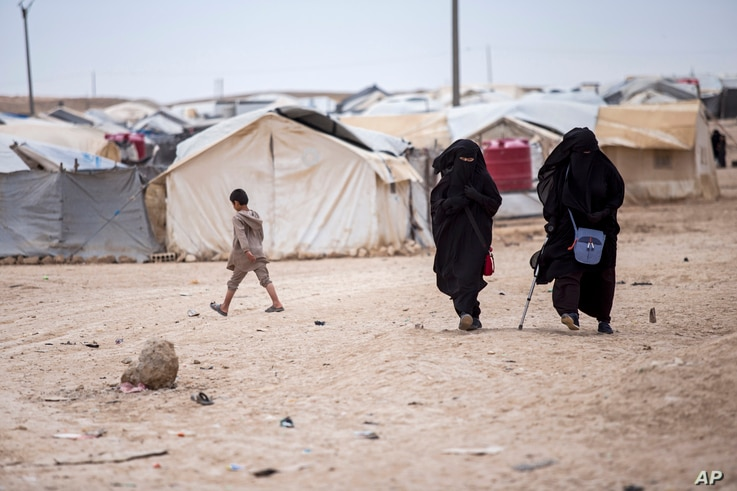 Women walk in the al-Hol camp that houses some 60,000 refugees, including families and supporters of the Islamic State group,…