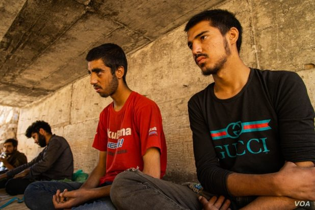 Zaki Wassim, 17, at right, sits beside his brother under the bridge. Both of them are trying to reach Istanbul for the second time, after being sent back to the Iranian border by Turkish police a few weeks ago. (VOA/Yan Boechat)