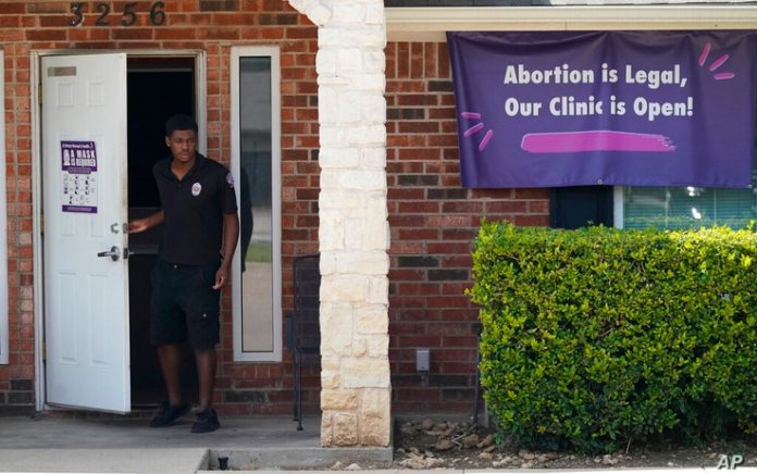 File-In this file photo from September 1, 2021, a security guard opens the door to the Whole Women's Health Clinic in Fort Worth,...