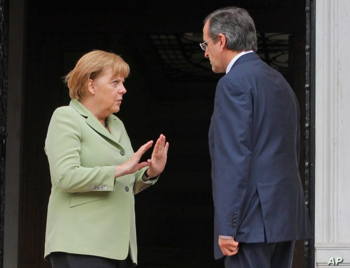 File - Greek Prime Minister Antonis Samaras, right, and German Chancellor Angela Merkel speaking at the Maximos Palace in Athens, October 9, 2012.