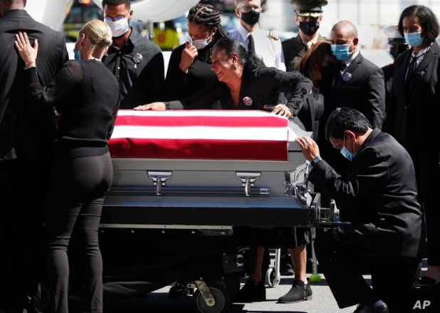 Family members of U.S. Marine Sgt. Johanny Rosario Pichardo grieve upon the arrival of his casket at Logan Airport in Boston, Sept. 11, 2021.