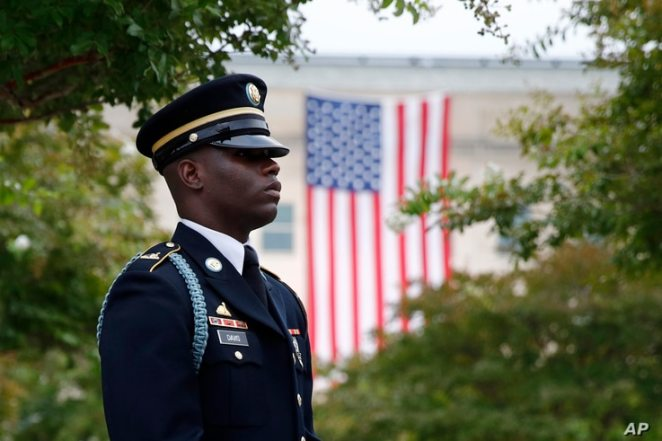 A member of the U.S. Army Old Guard stands on the grounds of the National 9/11 Pentagon Memorial before a ceremony in observance of the 18th anniversary of the September 11th attacks at the Pentagon in Washington, Wednesday, Sept. 11, 2019. (AP…
