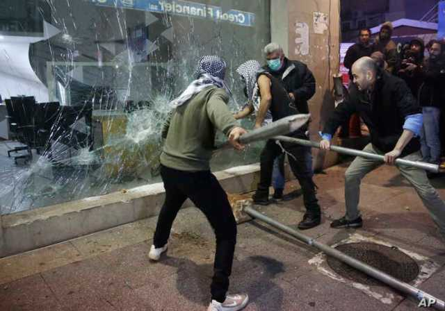 Anti-government protesters smash a bank widow, during ongoing protests against the Lebanese central bank's governor and against…