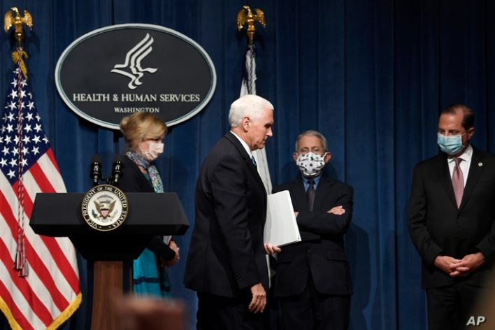 Vice President Mike Pence, second from left, walks off of the stage following the conclusion of a briefing with the Coronavirus…