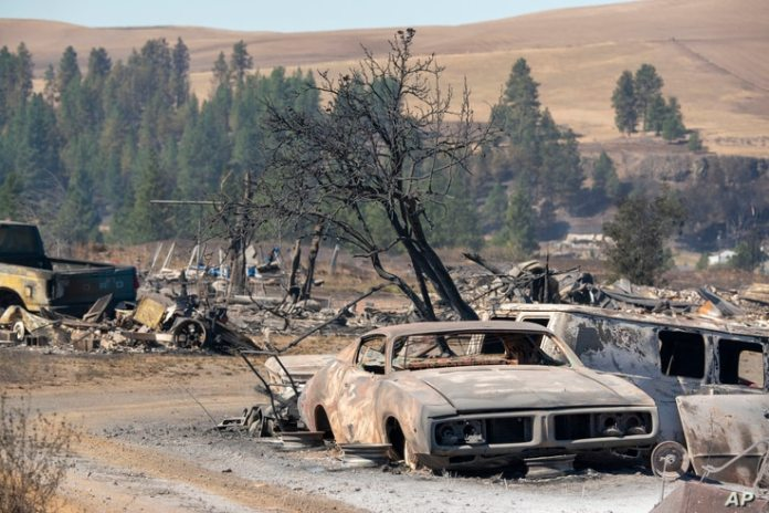 Vehicles destroyed by a wildfire are shown Tuesday, Sept. 8, 2020, in Maldin, Wash. (AP Photo/Jed Conklin)