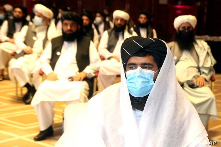 A member of Taliban negotiation delegation, keeps his face mask during the opening session of the peace talks between the…