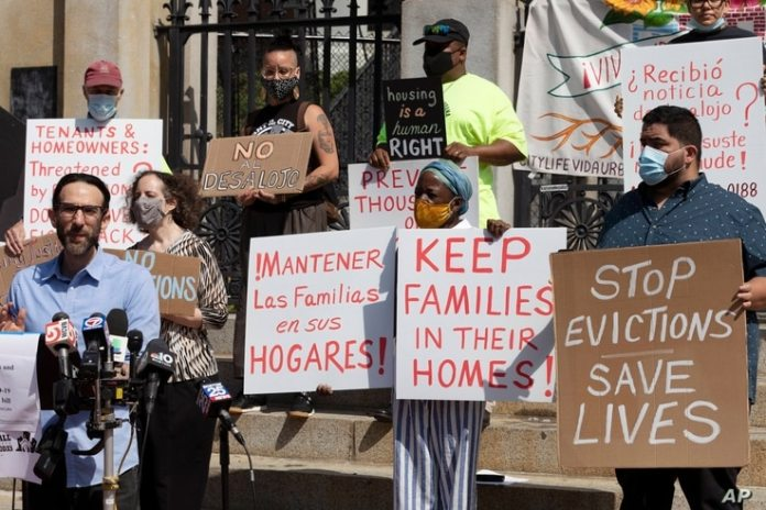People from the Coalition of Housing Justice groups hold a sign protesting evictions during a press conference outside ...