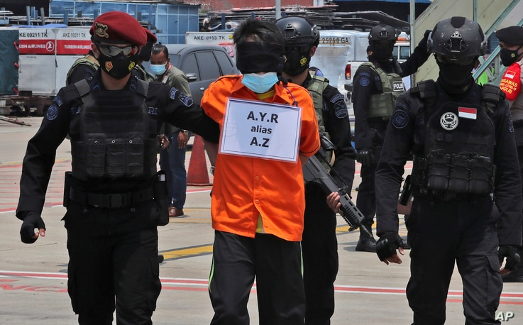 Police escort a suspected militant upon arrival at the Soekarno-Hatta International Airport in Tangerang, Indonesia, Thursday,…