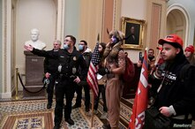 FILE PHOTO: Police speak to supporters of U.S. President Donald Trump, including Jacob Chansley, also known as Jake Angeli, in…