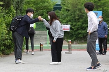 A senior student, left, is greeted by a teacher upon his arrival at the Kyungbock High School in Seoul, South Korea, Wednesday,…