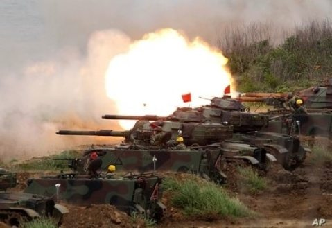 FILE- In this May 25, 2017, file photo, a line of U.S. M60A3 Patton tank fire at targets during the annual Han Kuang exercises on the outlying Penghu Island, Taiwan.