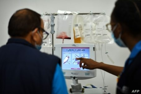 Staff check a monitor as a donor gives blood plasma at a newly opened plasma donor centre in Twickenham, southwest London on…