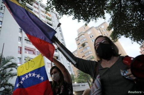 Supporters of Venezuelan lawmaker Juan Requesens shout slogans in front of his house after he was put on house arrest in Caracas