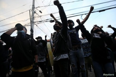 People protest outside a police station after a man, who was detained for violating social distancing rules, died from being repeatedly shocked with a stun gun by officers, according to authorities, in Bogota