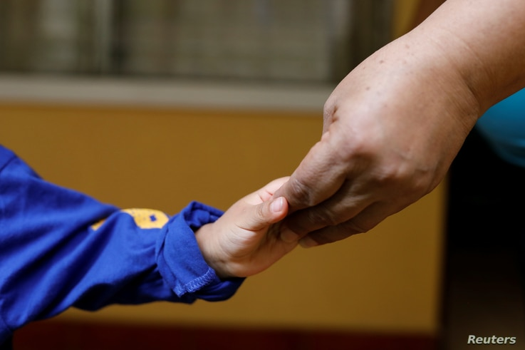 An unaccompanied child who was deported from the U.S. touches hands with his carer at a shelter in Guatemala City, Guatemala…