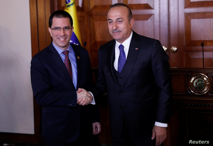 Turkish Foreign Minister Mevlut Cavusoglu (R) shakes hands with his Venezuelan counterpart Jorge Arreaza after a press…