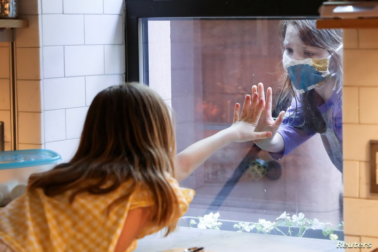 Lydia Hassebroek says hi to her friend Rose through her kitchen window during the outbreak of the coronavirus disease (COVID-19…