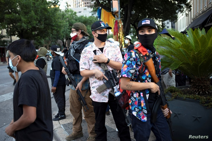 """A Texas Guerrillas member who calls himself, """"Apex,"""" third from right, and others carry weapons at a Black Lives Matter rally…"""