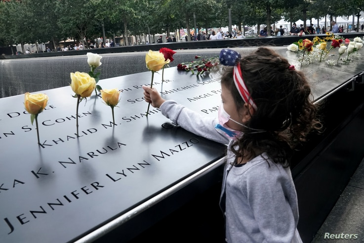 A girl places a flower on the edge of the North pool during ceremonies on the 19th anniversary of the September 11, 2001…