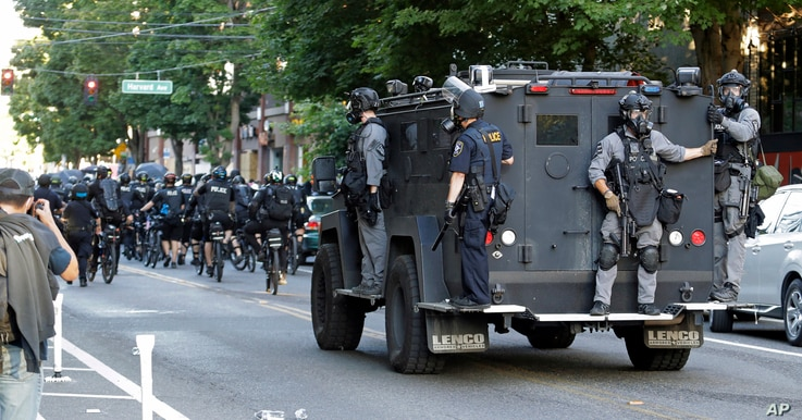 Seattle Police ride on a vehicle behind bicycle police during a Black Lives Matter protest march, Saturday, July 25, 2020, in…