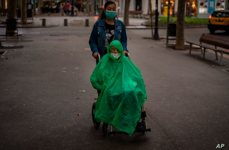 A man wearing a face mask and rain cover is pushed in a wheelchair along a boulevard in Barcelona, Spain on Wednesday Sept. 9,…