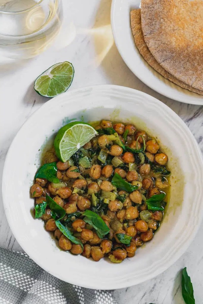 chickpea curry recipe with basil, coconut milk, and lime in white bowl and pita bread