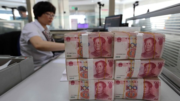 Renminbi banknotes are placed on a bank staff's table in a bank in Lianyungang, east China's Jiangsu province on August 11, 2015. China's central bank on August 11 devalued its yuan currency by nearly two percent against the US dollar, as authorities seek to push market reforms and bolster the world's second-largest economy. CHINA OUT AFP PHOTO (Photo credit should read STR/AFP/Getty Images)
