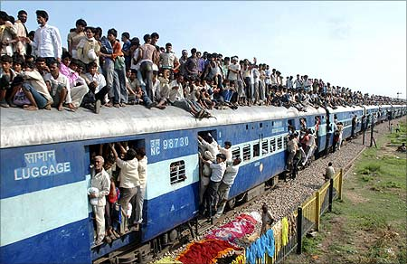 Devotees travel on a crowded passenger train to take part in the