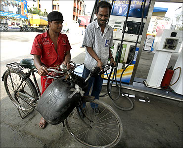 A worker (R) fills plastic containers with petrol at a pump in Kolkata.