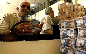 A client counts his money near a bank's teller. Photograph: Bassim Shati/reuters