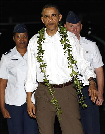US President Barack Obama has a lei placed around his neck as he arrives for a vacation in Hawaii