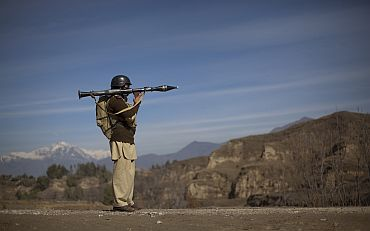 Pakistani soldier Hamed holds a rocket launcher while securing a road in Khar, the main town in Bajaur Agency, in Pakistan