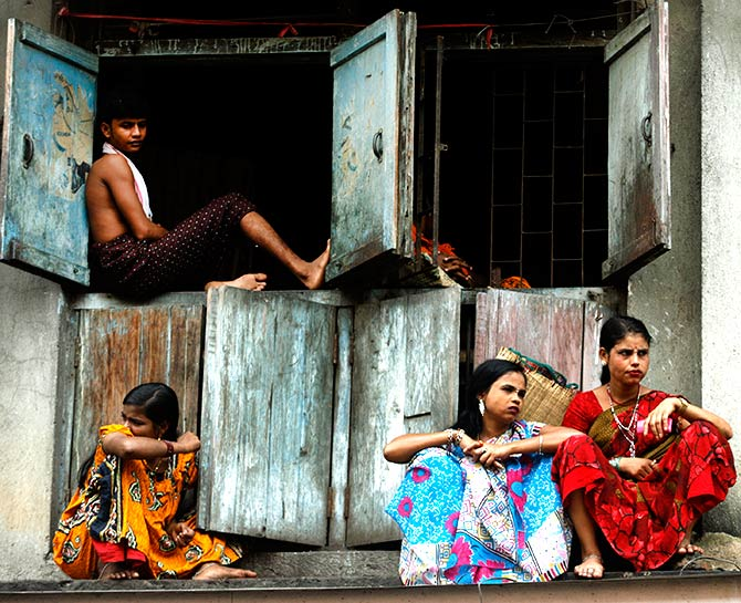 Sex workers sit outside their cramped quarters in Mumbai's red light district.
