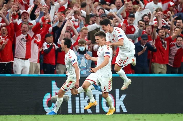 Joakim Maehle celebrates with teammates Thomas Delaney and Christian Norgaard after scoring Denmark's fourth goal.