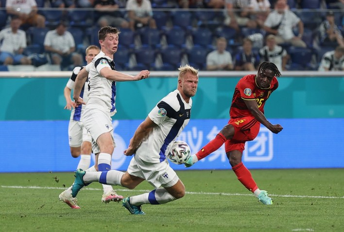 Belgium's Jeremy Doku essays a shot at goal while challenged by Finland's Paulus Arajuuri.