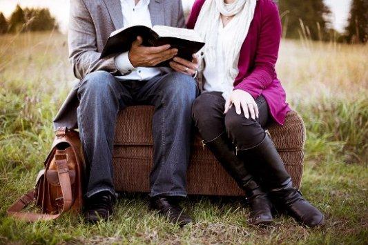 Pareja leyendo un libro en el parque.