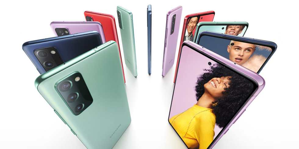 Eleven Galaxy S20 FE 5G phones standing upright in a circle, alternating Cloud Navy, Cloud Red, Cloud Lavender, and Cloud Mint. Some are seen from the rear and some are seen from the front, with photos of people onscreen. Each person stands against a color background that matches the color of the phone.