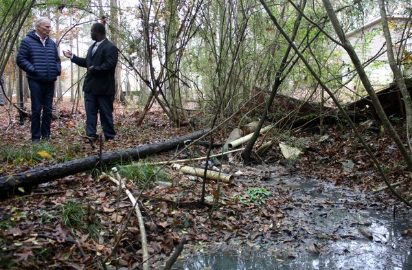 Aaron Thigpen, a Fort Deposit activist, shows UN Special Rapporteur Philip Alston (left) a place in Lowndes County where two homes discharge raw sewage into an open-air pool via exposed PVC pipes. One home's water line runs right through the fetid area. (Connor Sheets | csheets@al.com)