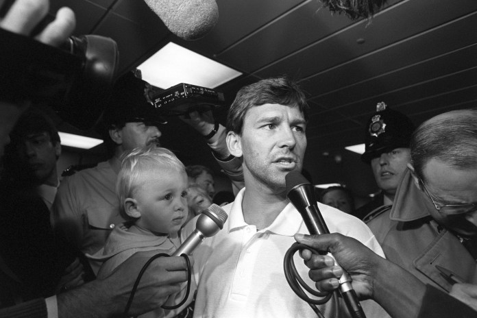 Robson, with his son Ben, talks to the media at Manchester Airport after Italia '90