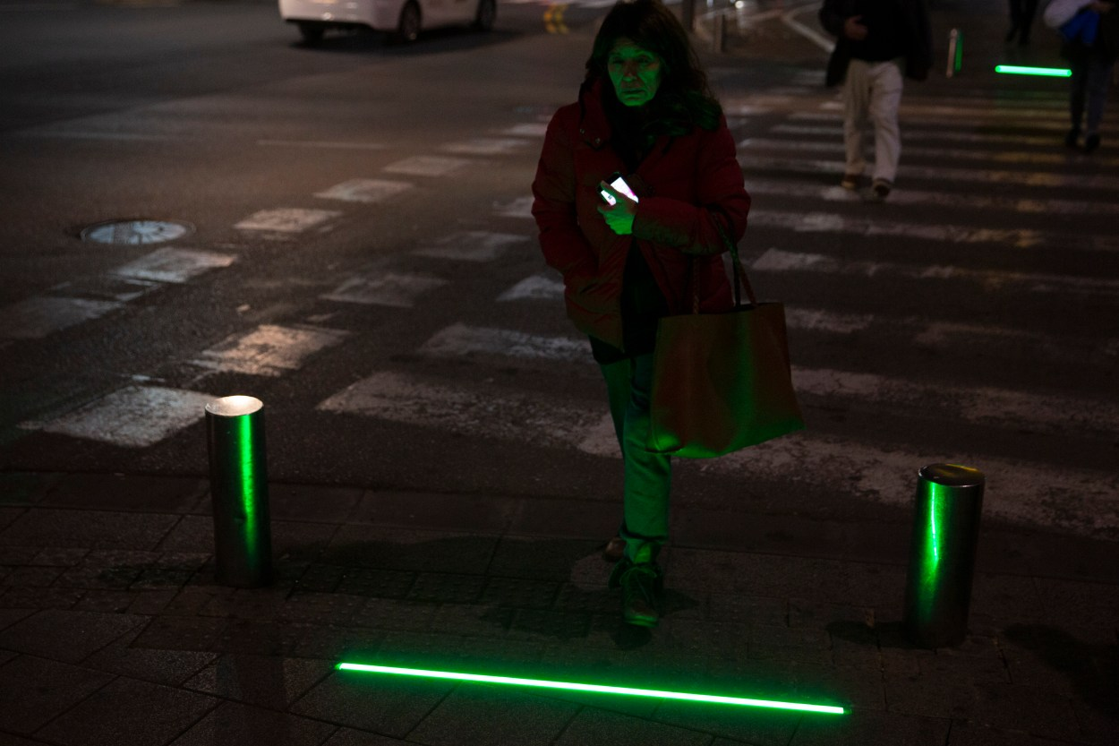 An Israeli woman walks past embedded LED lights at a crossing in Tel Aviv