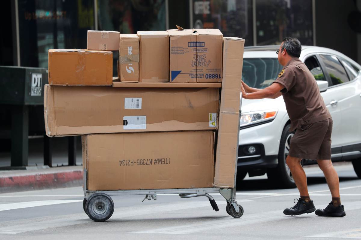 A UPS driver pushes a load of packages from his truck to a building in downtown Los Angeles, California, July 22, 2019.