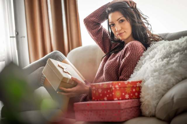 A young beautiful girl opens the gift in a cozy Christmas atmosphere