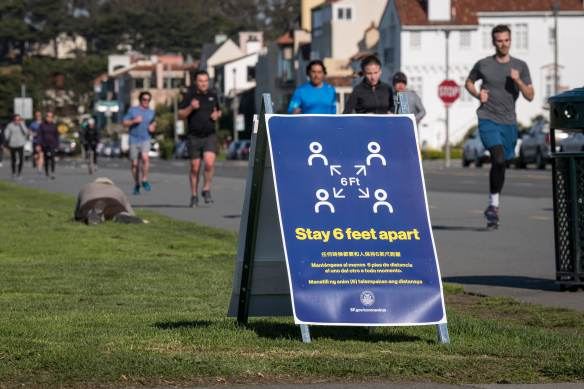 A sign informing people to stay 6 feet apart stands on Marina Boulevard at Marina Green in San Francisco, California, U.S., on Wednesday, March 25, 2020.