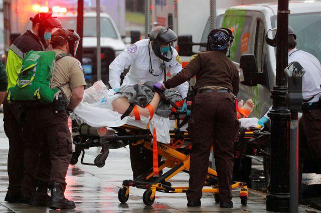 Lekarze Boston EMS pracują nad reanimacją pacjenta w drodze do karetki pogotowia podczas wybuchu epidemii koronawirusa (COVID-19) w Bostonie, Massachusetts, 27 kwietnia 2020 r.